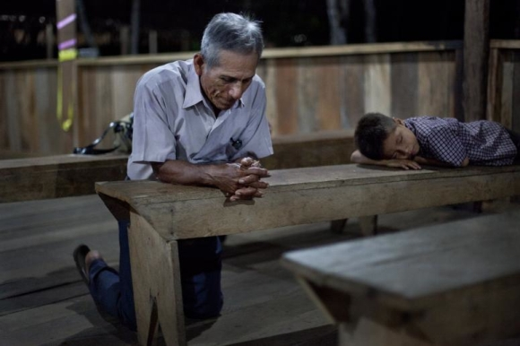 "Edison Romero, 72, kneels in prayer while attending a missions training session at the School of Cross-cultural Missions near Iquitos, Peru, in the Amazon jungle. As he prays, the child of a fellow student sleeps on a nearby bench. Romero's wife of 44 years died just three days before the training began, but he still traveled 12 hours by boat from his village to attend. Romero said he ""just couldn't miss it."" Photo by Rebecca Springer"