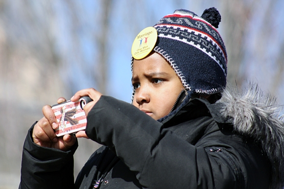 "Nine-year-old Denzel Brown of Aurora snaps a photo during one of the speeches. Brown wore one of the yellow buttons supporting ""Marriage: One Man One Woman."""