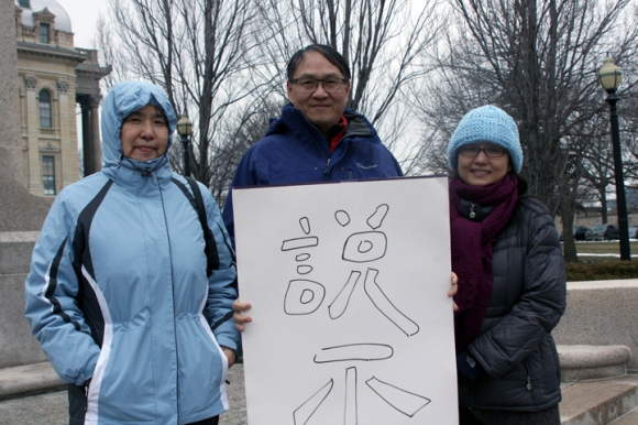 "Esther Wang and John and Grace Chao pose with a sign reading ""Vote No"" in Chinese characters."