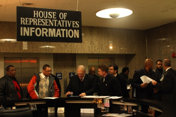 Rev. Bob Vanden Bosch (third from left) of Concerned Christian Ministries helps people locate their representatives' offices at the Stratton Building in downtown Springfield.