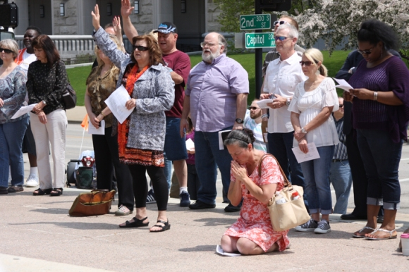 At a worship service on the National Day of Prayer, some knelt in prayer in front of the Illinois State Capitol, while others lifted their hands in worship.