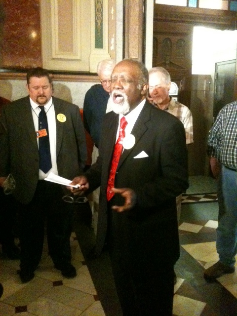 Pastor Danny Holliday prays at a pro-traditional marriage rally in the Illinois Capitol rotunda.