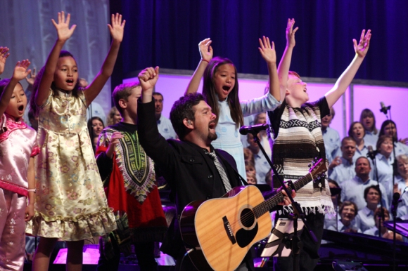 """Children in costumes representing nations around the world join FBC Houston's praise team and choir to sing a moving version of  """"How Great is Our God""""."""