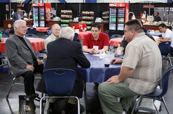 Illinois Baptist pastor Adam Cruse (center, in red) talked with friends in the exhibit hall, including Illinois' own Sons of the Father gospel group.