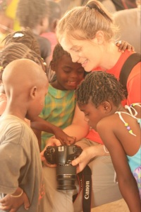 Kids in Haiti crowd around to see themselves in a camera's tiny screen.