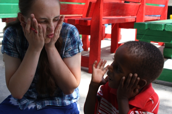 Abby Fleischer speaks a universal language - funny faces - with a child at New Life.