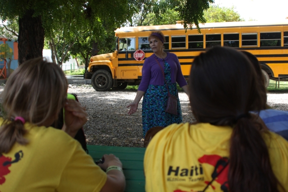 New Life's guest house coordinator, Lisa, shares the rules with the team. (The bus behind her was our transportation from the airport to the children's home.)