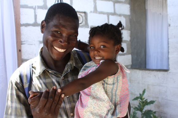 Thomas Ogens, who helped coordinate the building projects and deliver supplies, with Pastor Estephat's daughter.