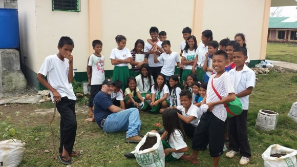 Kurt Crail, a volunteer from Ashmore Baptist Church, visits with school kids on Gibitngil Island in the Philippines.