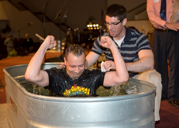 After being baptized in a horse trough, David Vittetoe celebrates as John Howard, minister to students, assists. The troughs gave the church three locations to baptize the 103 people who came forward.