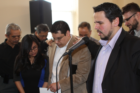 Starting Point in Chicago: Pastor Marvin del Rios of Iglesia Bautista Erie (right) prays for the new congregation his church is sponsoring, led by Pastor Jonathan de la O and his wife, Emely, surrounded by leaders from Chinese, Korean, and Romanian church plants who attended the April 6 launch service.