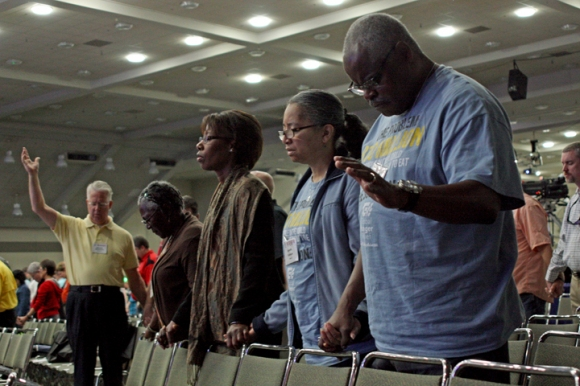 Christopher and Annette Robinson (right) pray alongside Linda Woods-Smith and Inez Parker at the Southern Baptist Convention in Baltimore. All four are Broadview Missionary Baptist Church.