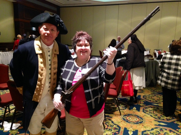 Lisa Sergent holds a musket used by a private who served under General George Washington. It is owned by history buff and pastor Dan Fisher (left).