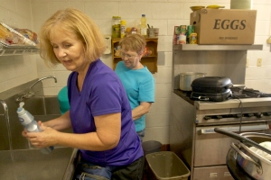 Lois Dodson and Karen Watson clean up after lunch at Light of Christ Church.