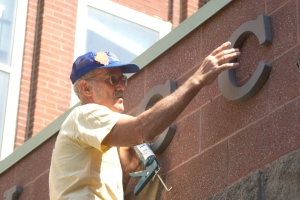 "Leroy Burnett adds ""LOCC"" lettering to the outside of the church's building."