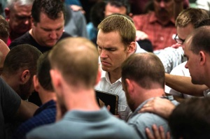 At a meeting in Asia, young missionaries surround new IMB President David Platt to pray for him as he seeks to mobilize churches. Photo by Hugh Johnson/IMB
