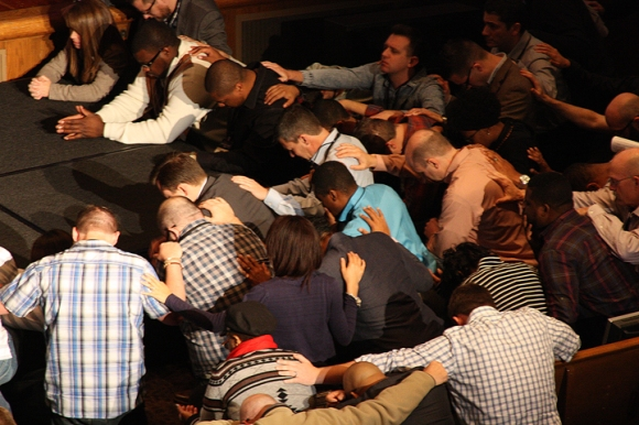 Summit attenders gathered in the aisles and at the altar to pray together at the start of a March meeting on racial reconciliation and the gospel.