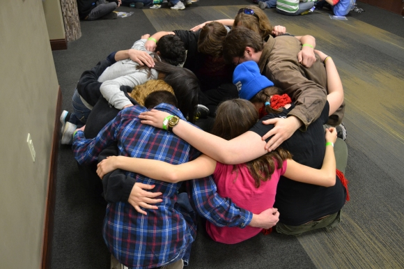 Students at Youth Encounter 2014 huddle for prayer after a main session of the annual evangelism conference. Photo by Brooke Kicklighter