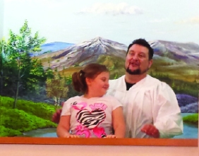 Pastor Brad Sloan baptizes his daughter, Delaney, at Dahlgren Baptist Church.