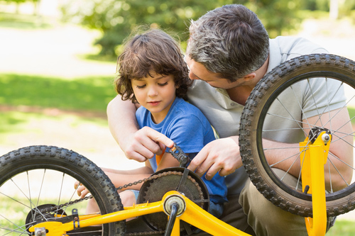 Close-up of father and son fixing bike